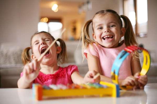 Fotografía de unas niñas riendo y tocando instrumentos musicales