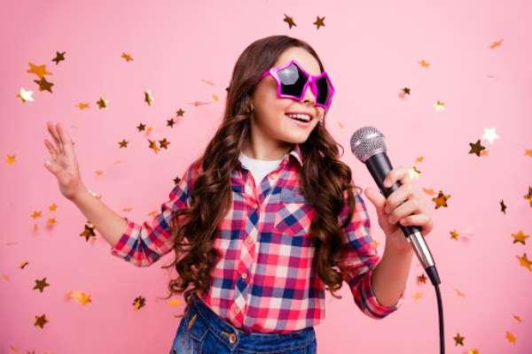 Fotografía de una niña cantando con un micrófono con fondo rosa