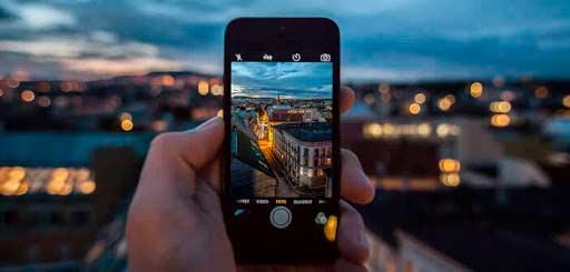 una persona sostiene un iPhone mientras hace una fotografía